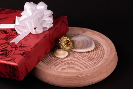 Anniversary gift concept. Cocktail ring with decorated red giftbox and seashell on sand stone with dark background