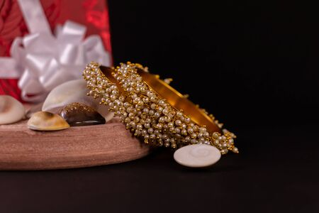 Gold plated pearl bangles with seashells and decorated gift box on black background. Traditional gift concept