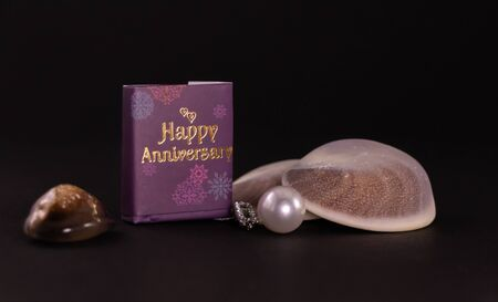 Anniversary gift concept. Beautiful pearl necklace with happy anniversary mini message book and seashells on black background