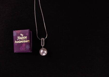 Beautiful pearl pendant necklace and happy anniversary mini message book on black background. Anniversary gift concept