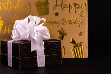 Brown lether box decorated with white ribbons and carry bag on black background. Birthday gift concept Stok Fotoğraf