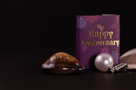 Silver pearl necklace and happy anniversary mini book with seashells on black background. Anniversary gift concept Stok Fotoğraf