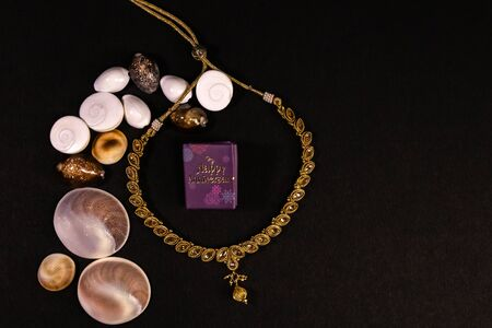 Anniversary gift concept. Beautiful golden necklace with spreaded seashells and happy anniversary mini message book on black background Stok Fotoğraf