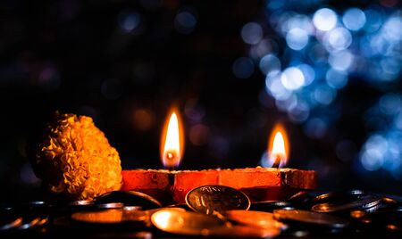 Side view of a pair of glowing Terracotta lamps with flower and coins, and blue colored bokeh in the background. Prosperity concept Stock Photo