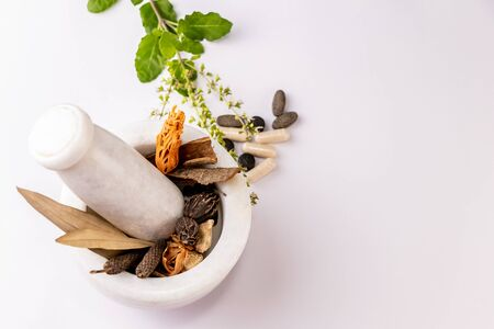 Collection of different spices and herbal tablets with tulsi leaves in white mortar pestle on white background. Herbal and ayurvedic concept