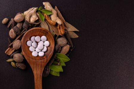 Wide shot of white herbal tablets in a wooden spoon with scattered whole herbs and copy space on black background Stock Photo