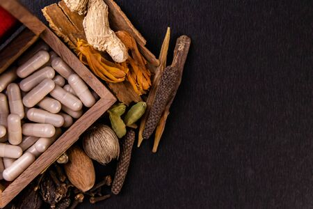 Ayurvedic drugs in a wooden box and assorted spices on black background. Herbs concept