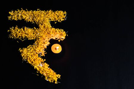 top view of tea lamp glowing with rupee sign made with flower petals on black background and copy space. financial concept