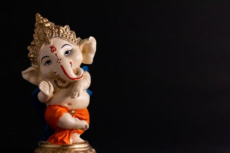 beautiful photography of ganesha statue in front of black background, wisdom concept