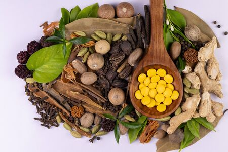 Ayurvedic medicine concept. Top view of herbal drugs in wooden spoon, scattered spices and green leaves on white background