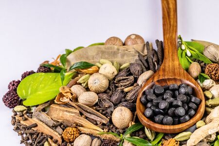 close-up of variety of spices with green leaves and herbal drugs in wooden spoon on white background