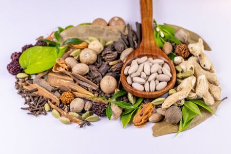 Front view closeup shot of herbal tablets in a wooden spoon with scattered whole spices and herbs in the background