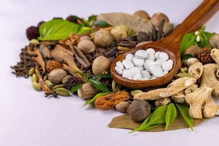 High angle shot of white tablets in closeup with dried herbs and white surface in the background. Herbal and Unani concept
