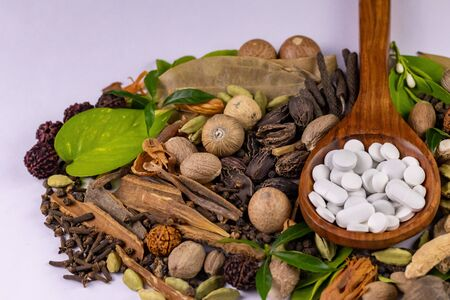 Macro shot of white Herbal tablets in a wooden spoon with scattered herbs and spices in the background. Unani Medicine concept