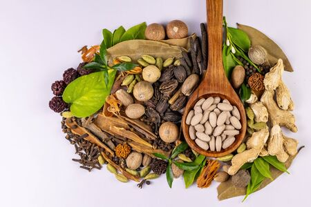 Top view of Assorted spices with green leaves and brown oval tabletsin a wooden spoon on white background