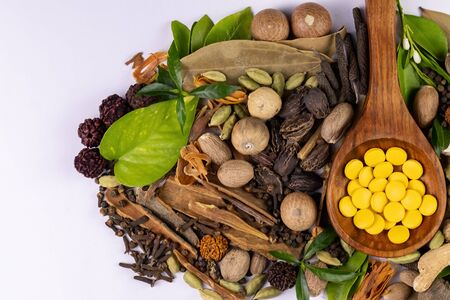 Top view of assorted spices with green leaves and herbal medicines in wooden spoon on white background.Ayurvedic treatment concept Banco de Imagens