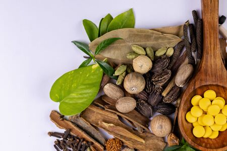 Ayurvedic medicine concept. Ayurvedic drugs in wooden spoon, assorted spices and green leaves on white background