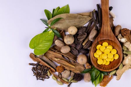 Alternative medicine concept. Yellow Ayurvedic tablets in a wooden spoon, dried herbs and green leaves on white background