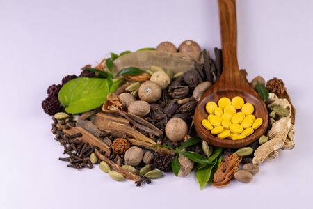 Traditional medicine concept. Top view closeup of  ayurvedic drugs in wooden spoon and spices on white background