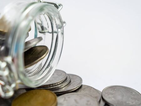 Extreme close up shot of a glass container having coins and white background with copy space