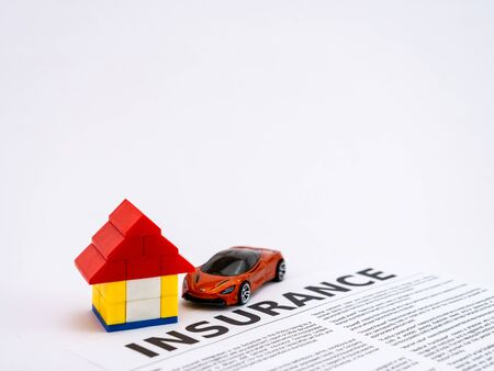 A car toy parked in the garage made of with insurance paper in bold fonts Banco de Imagens