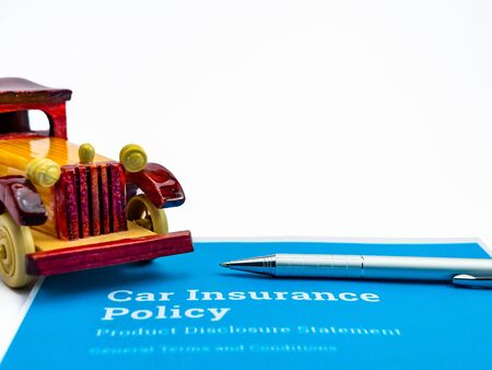 A silver ball pen and one wooden vintage toy car over blue insurance papers shot against white background