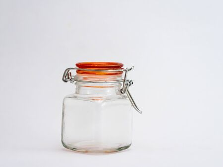 A small empty glass jar with orange lid shot agains white background and copy space 写真素材