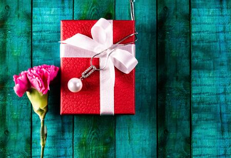 Top close up of a red gift box, pink carnations flower and a pearl neacklace on green background, Soulmates and wife concept