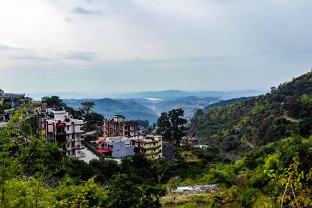 high angle shot of buildings situated on mountains and cloudy sky in the bacground