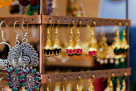 Close up of beautful jewellery hanging with hooks on the rack and a peacock shaped silver ear ring on the left