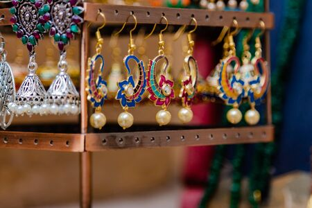 Close up shot of beautiful pearl ear rings on the display rack with blurred necklaces in the background