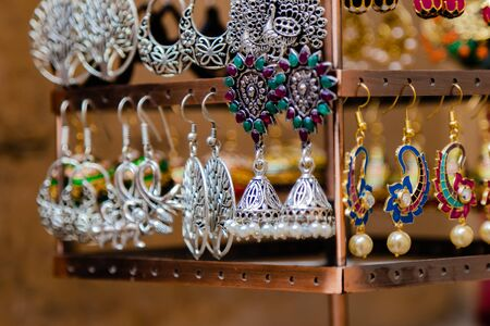 Close up shot of beautiful stone and silver ear rings hanging on the display rack