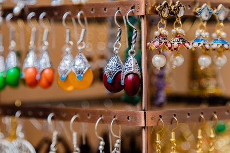 Close up shot of ethnic and designer ear rings in beautiful colors made with stone, pearl and metal Imagens