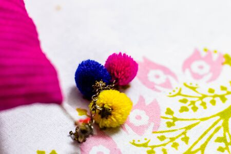 Close up shot of three woolen pom pom of pink, yellow and blue attached with a key chain