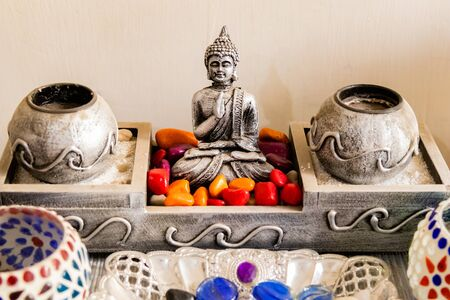 Front close up of shot of a Buddha statue with colored stones and beautiful spherical cups in Interior decoration concept