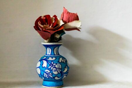 Front close up shot of a blue flower vase with red colored flowers made of craft paper and copy space on the right side of frame