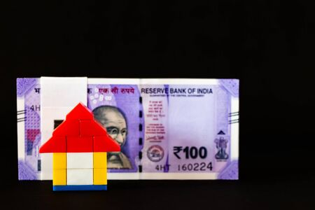 Close up of a home with money bundle blurred behind in house loan concept