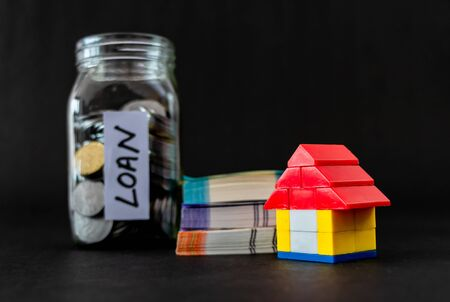 Close up shot of a toy house with money notes and coin filled glass jar defocused in background
