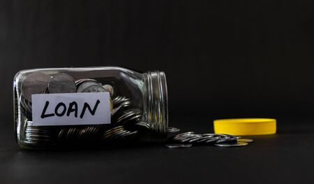 Coins empty out from a glass jar in Loan concept shot against black background and yellow cap aside