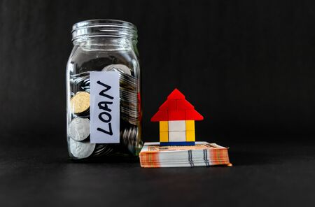 Front parallel shot of a toy home on money notes, coins in glass jar and black background with copy space