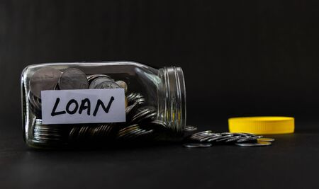 Glass jar full of coins fallen on ground with yellow cap, black background and LOAN label