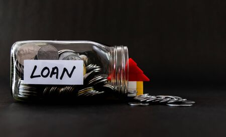 Glass jar of coins fallen down with LOAN label and colorful house behind shot against black background