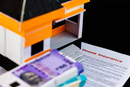High angle close up of House insurance papers under a model house and blurred money bundles Imagens