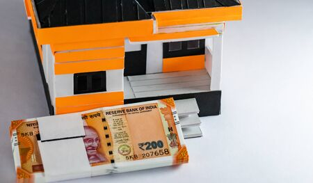 High angle close up shot of a house model with two hundred rupee bundles in home loan concept