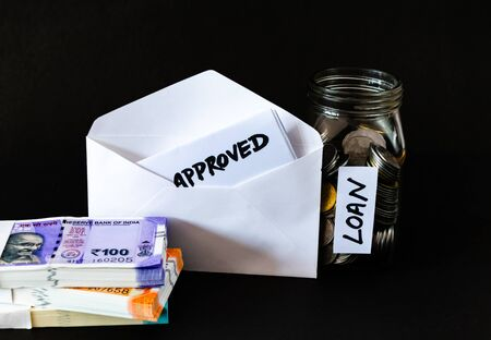 High angle shot of a glass jar, coins in it, money bundles and a white open envelope with the word approved Imagens