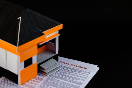 High angle shot of a home model with house insurance papers below, on black background Imagens