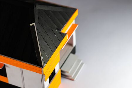 High angle shot of a home model with the black roof in focus and white surface illumintaed below