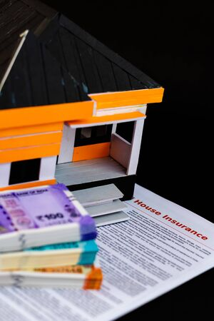 High angle shot of a house model with insurance papers below and defocused money bundles on the side