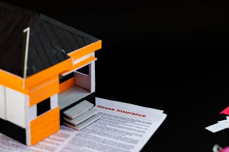 High angle shot of a house model with insurance papers below