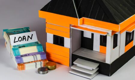 High angle shot of a house model with notes, coins and LOAN word on paper Imagens